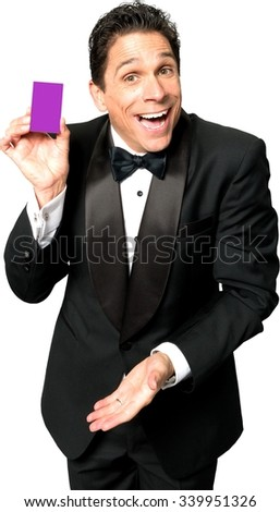 Excited Caucasian man with short black hair in evening outfit holding business card - Isolated - stock photo