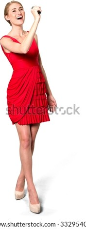 Excited Caucasian young woman with medium blond hair in evening outfit holding microphone and singing - Isolated - stock photo