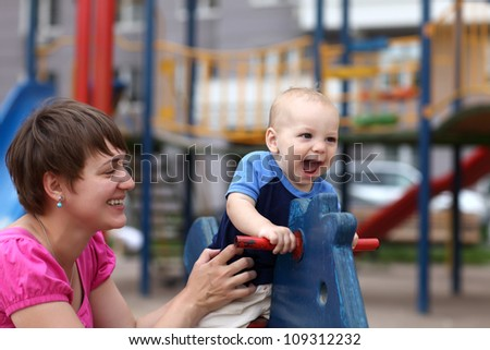 Excited child with his mother at the outdoor playground - stock photo