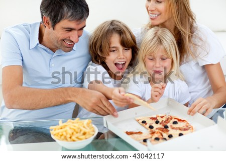 Excited children eating a pizza with their parents in the living-room - stock photo