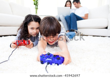 Excited children playing video games lying on the floor with their parents in the background - stock photo