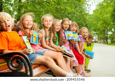 Excited children sitting on bench in a row