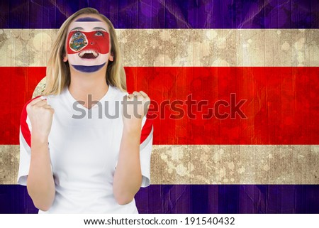 Excited costa rica fan in face paint cheering against costa rica flag in grunge effect - stock photo