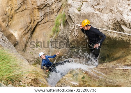 Excited couple climbing cliffs together in canyon. - stock photo