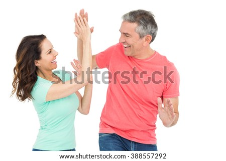 Excited couple giving a high-five on white background - stock photo