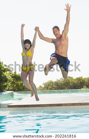 Excited couple jumping into swimming pool on holidays on a sunny day - stock photo