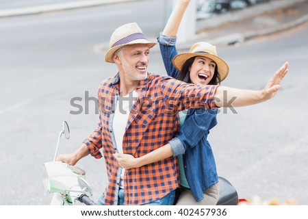 Excited couple waving hands on moped while riding in city - stock photo