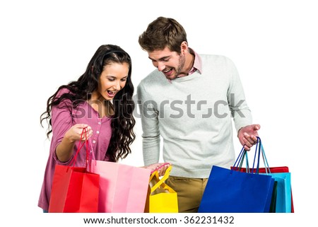 Excited couple with shopping bags on white background - stock photo