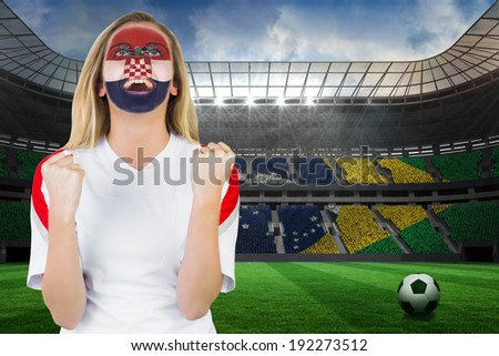 Excited croatia fan in face paint cheering against large football stadium with brasilian fans - stock photo