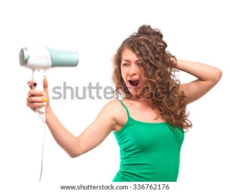 Excited curly young woman drying her hairs with drier. Isolated on white background.   Studio portrait isolated on white.  Beauty. Health care.