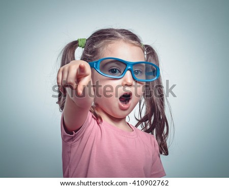 excited cute little girl with 3d glasses pointing her finger towards camera