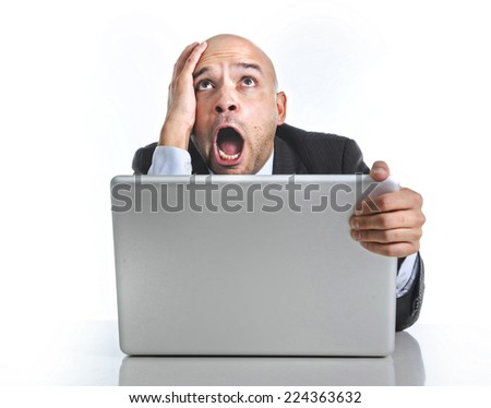 excited desperate businessman in stress at computer laptop holding monitor watching online finances drop down or loosing money on line gambling isolated on white background - stock photo