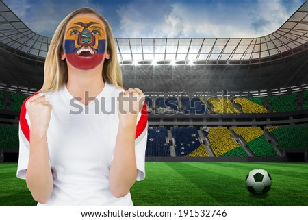 Excited ecuador fan in face paint cheering against large football stadium with brasilian fans - stock photo