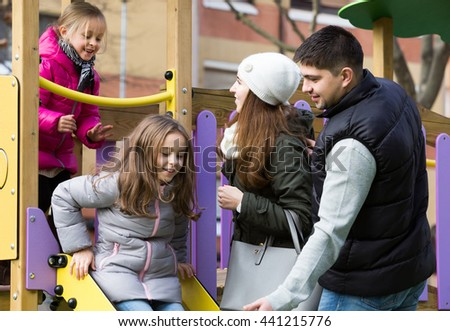 Excited european  parents with two daughters playing at children's slide - stock photo