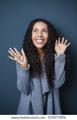Excited exuberant young African American woman smiling with delight and gesturing in the air with her hands, against dark blue - stock photo