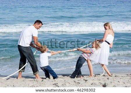 Excited family playing tug of war at the beach - stock photo