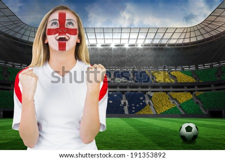 Excited fan england in face paint cheering against large football stadium with brasilian fans - stock photo