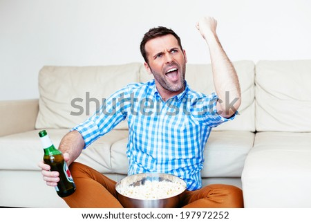 Excited fan watching his team's victory on tv - stock photo