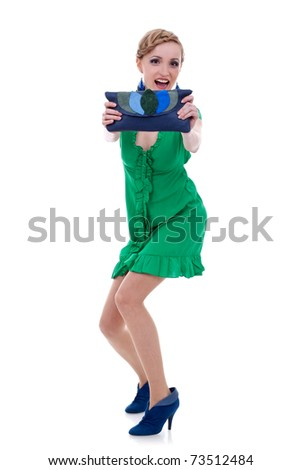 excited fashion woman in green dress showing a nice purse to the camera - stock photo