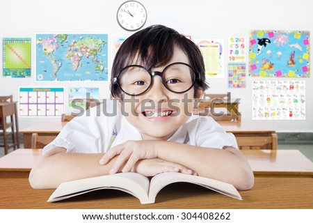 Excited female elementary school student wearing glasses in the class and smiling at the camera while reading a book on the table - stock photo