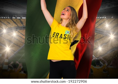 Excited football fan in brasil tshirt holding ghana flag against vast football stadium with fans in yellow - stock photo