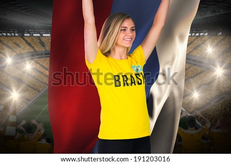 Excited football fan in brasil tshirt holding russia flag against vast football stadium with fans in yellow - stock photo