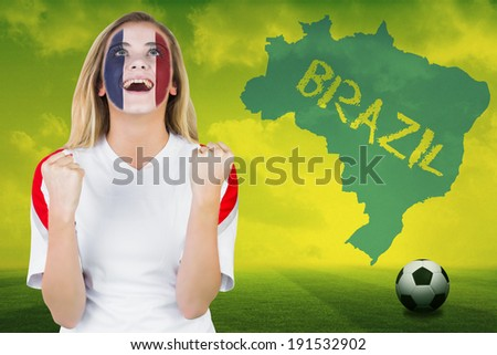 Excited france fan in face paint cheering against football pitch with brazil outline and text - stock photo