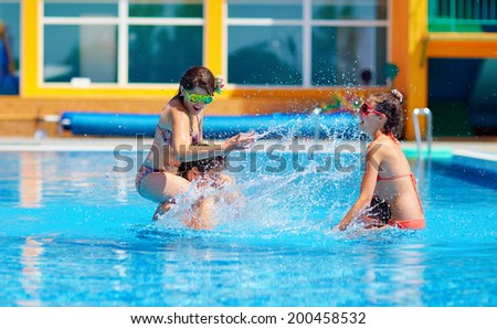 excited friends having fun in pool, water fight - stock photo
