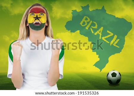 Excited ghana fan in face paint cheering against football pitch with brazil outline and text - stock photo