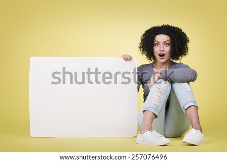 Excited girl being astonished by amazing news holding a blank white paper sign board with copy space. - stock photo