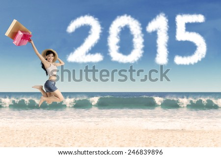 Excited girl holding shopping bag jump on beach celebrate new year of 2015 - stock photo