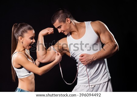Excited girl measuring bodybuilder's bicep. Young athletes on dark background. He's become much bigger. Athlete impresses female fan.