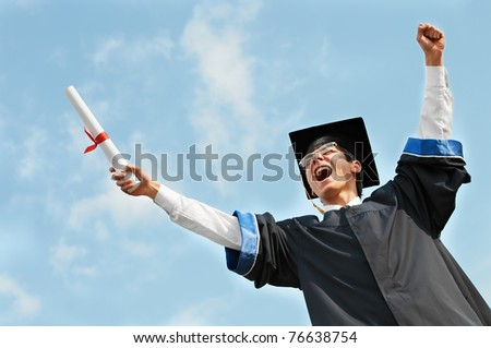 excited graduate student in gown with risen hands holding diploma over blue sky - stock photo