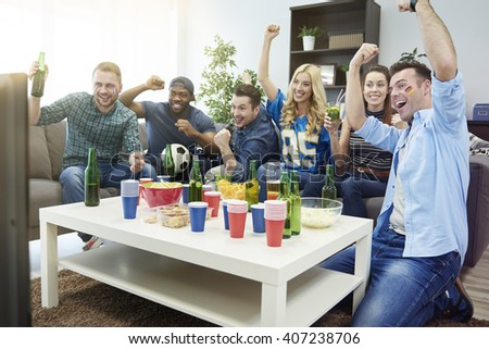 Excited group of friends watching sport on tv - stock photo