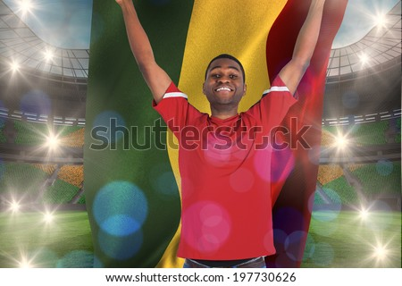 Excited handsome football fan cheering holding ghana flag against large football stadium with brasilian fans - stock photo