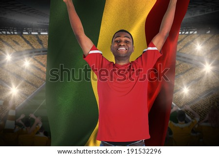 Excited handsome football fan cheering holding ghana flag against vast football stadium with fans in yellow - stock photo