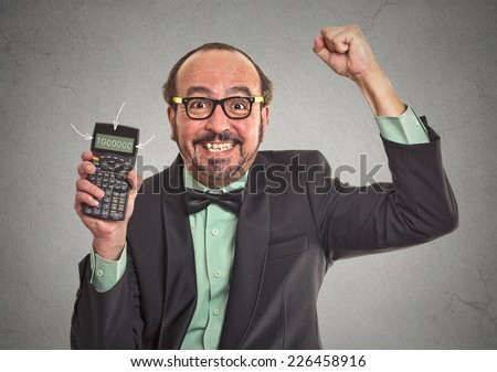 Excited happy businessman showing calculator with million number sign on screen isolated on grey wall office background. Human face expression emotion feeling. Economy financial wealth concept  - stock photo