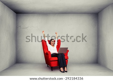 excited happy businesswoman with raised hands up sitting on the red chair and looking at laptop in grey empty concrete room - stock photo