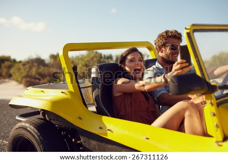Excited happy couple enjoying road trip in their open top car. Man driving the car young woman taking a selfie from her mobile phone. - stock photo