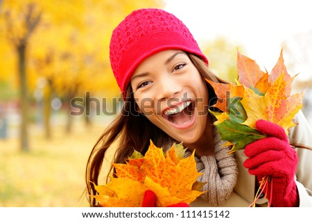Excited happy fall woman smiling joyful and blissful holding autumn leaves outside in colorful fall forest. Beautiful energetic mixed race Caucasian / Asian Chinese young woman. - stock photo