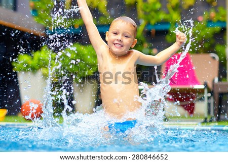 excited happy kid boy jumping in pool, water fun - stock photo