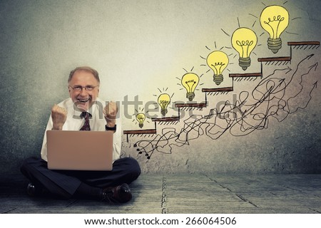 Excited happy senior executive man working on computer sitting on a floor in his office celebrates business success, promotion, company growth isolated on gray wall texture background  - stock photo