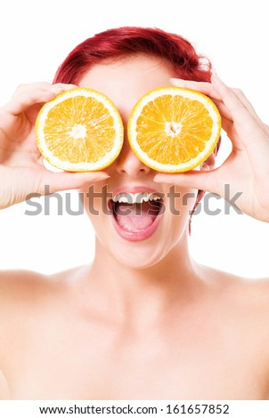 excited happy young redhead woman holding oranges over her eyes on white background - stock photo
