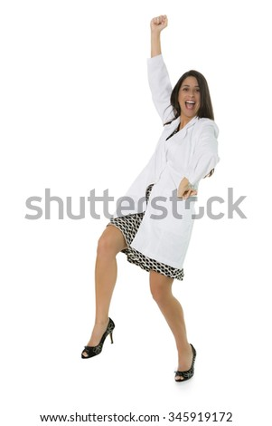 Excited Hispanic female wearing lab coat gesturing with fist in air on white background - stock photo