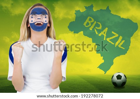 Excited honduras fan in face paint cheering against football pitch with brazil outline and text - stock photo