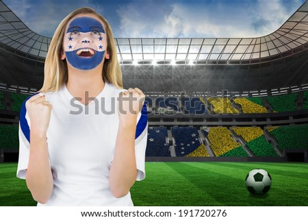 Excited honduras fan in face paint cheering against large football stadium with brasilian fans - stock photo
