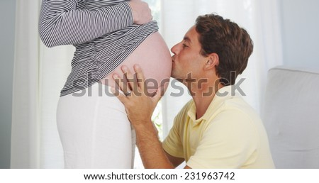 Excited husband kissing pregnant woman's belly - stock photo
