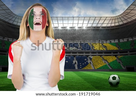 Excited italy fan in face paint cheering against large football stadium with brasilian fans - stock photo