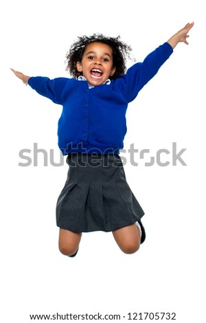 Excited jubilant school kid jumping high up in the air after hearing her annual result.