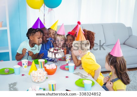Excited kid enjoying a birthday party blowing out the candles - stock photo